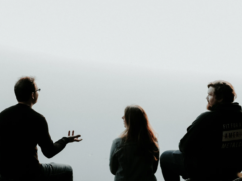 silhouettes of three people discussing argumentacijske pogreške